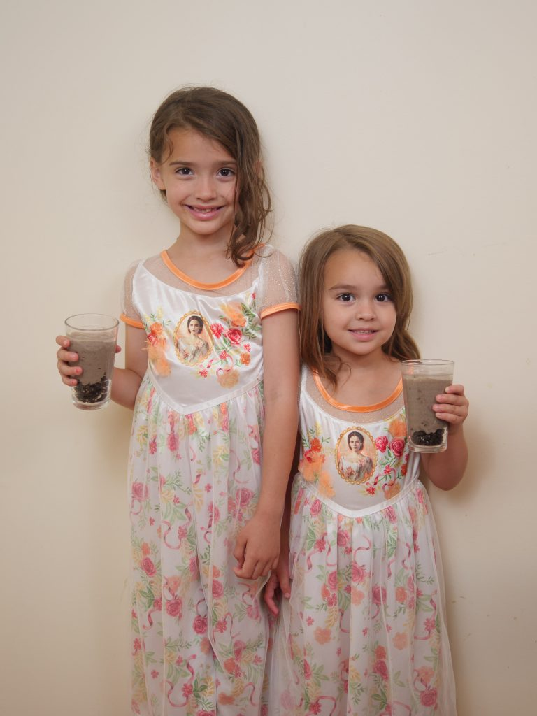 My children enjoying themselves at our household movie premier of the 'Beauty and the Beast' blu-ray. They are wearing Belle dresses and eating gray stuff!