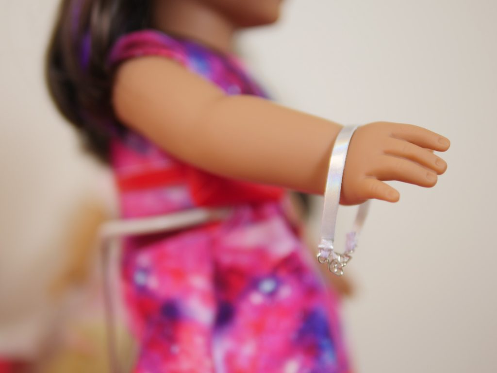 American Girl Luciana Vega has a silver bracelet to match her silver shoes.