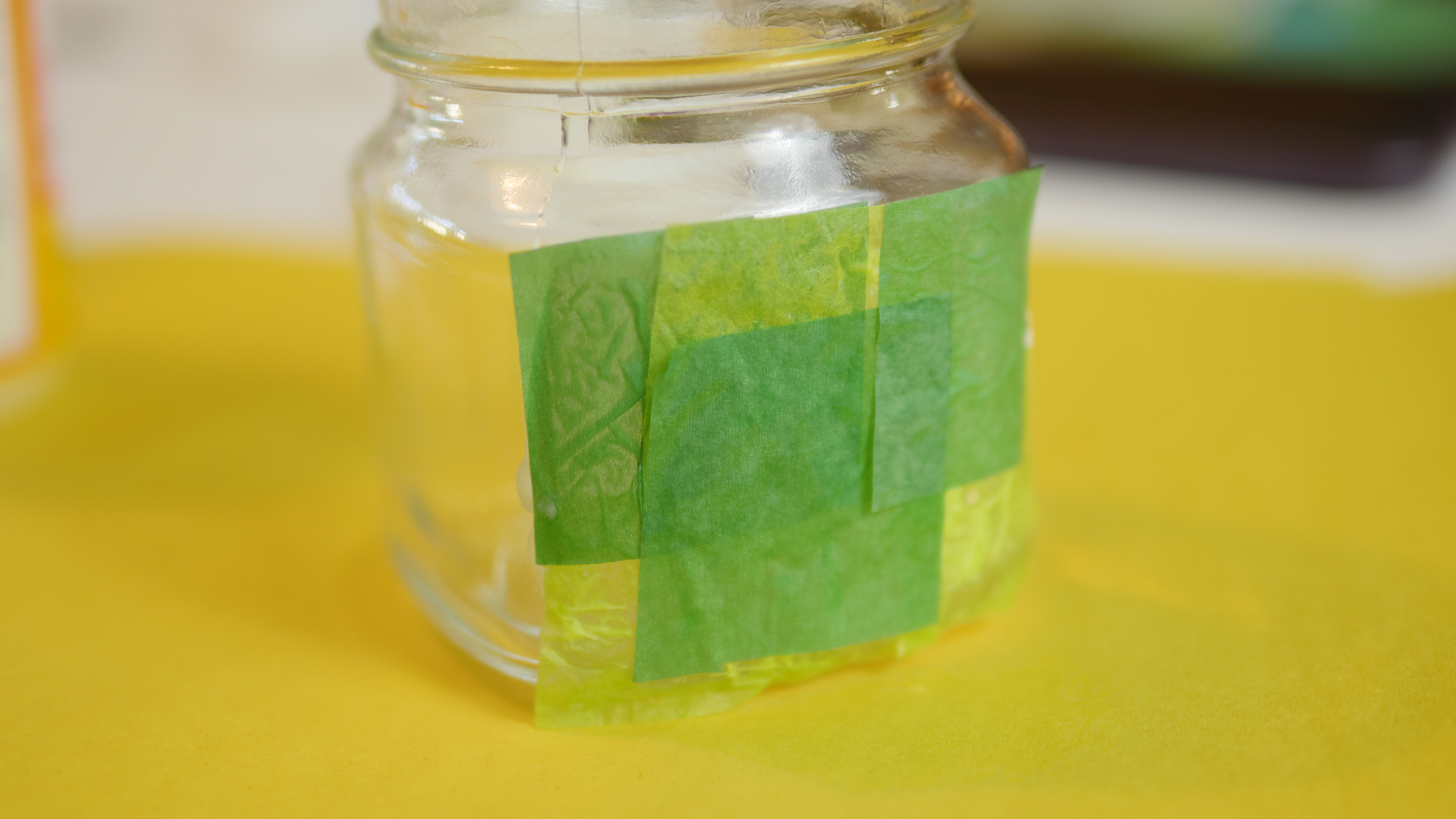 By re-using your old tissue paper, you can make a beautiful St. Patrick's Day candle centerpiece for your table. Work in small sections to make your candle holder look good.